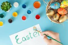 Kosz z ręcznie robiony Wielkanocnymi jajkami obok multicolor ręki z muśnięciem i farb które malują Wielkanocnego jajko na białej  obraz royalty free