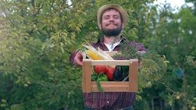 Kosz z warzywami w rękach szczęśliwy rolnik podczas zbierać na tle zieleni drzewa przy ogródem zbiory wideo