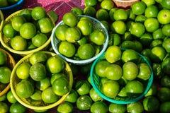 Kosze świeżego zaokrąglonego organicznie wapna owocowy tło w jaskrawego koloru żółtego i zielonego koloru sprzedawaniu w rynku po Obraz Stock
