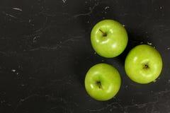 Koszt stały strzelający - trzy zielonego jabłka na czerni desce, przestrzeń dla teksta na lewej stronie zdjęcia royalty free