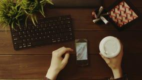 Koszt stały strzał mężczyzna dopatrywania fotografie na smartphone i pić herbacie zdjęcie wideo