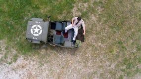 Koszt stały, truteń, patrzeje w dół na Męskim dowóca wojskowy w jednolity odpoczywać na plecy pojazd wojskowy Obrazy Royalty Free