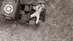 Koszt stały, truteń, patrzeje w dół na Męskim dowóca wojskowy w jednolity odpoczywać na plecy pojazd wojskowy Zdjęcie Royalty Free