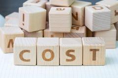 Kosztu, kosztu lub firmy zysk, i straty pojęcie, sześcian drewniany bl zdjęcia stock