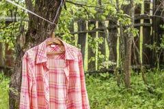 Koszula wiesza a na wieszaku na arkanie przeciw tłu stary fotografia stock
