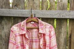 Koszula wiesza a na wieszaku na starym ogrodzeniu od desek w villag zdjęcie stock