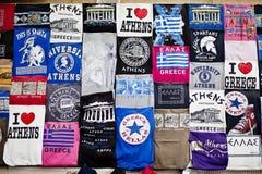 Koszulka merchandising z commo Ateny Grecja, Tshirts - Kwietnia 19, 2015 pamiątkarski sklep w kapitale Grecja przy Ateny Plaka - Fotografia Stock
