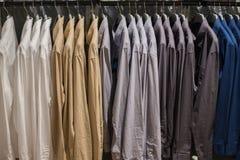 Koszulowy obwieszenie na poręczu przy Odzieżowym sklepem Zdjęcie Royalty Free