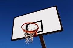 Koszykówka obręcz przeciw niebieskiemu niebu w boisku Zdjęcia Stock