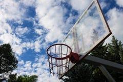 Koszykówka pierścionek przeciw niebu z chmurami i drzewami zdjęcia stock