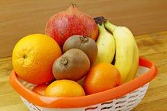 Koszykowe i świeże owoc na drewnianym stole Zdjęcie Stock