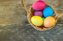 Koszykowy pełny kolorowi Easter jajka na drewnianym stole Obrazy Stock