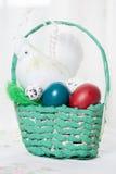 Koszykowy pełny z barwionymi Easter jajkami na stole Fotografia Stock