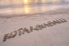 Kota Kinabalu handwritten on a sand beach royalty free stock images