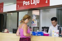 Kota Kinabalu Sabah Malaysia - Augusti 26th, 2017: En oidentifierad turist- dam som hjälps av en räknarepersonal Pos. Laju Mala Arkivfoton