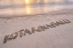 Kota Kinabalu scritto a mano su una spiaggia di sabbia Immagini Stock Libere da Diritti
