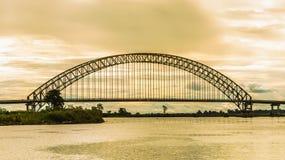Arch bridge at dawn. Kotabangun arch bridge crossing Mahakam river at dawn, Borneo, Indonesia Royalty Free Stock Image