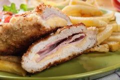 Kotelett Cordon bleu mit Schweinelende diente mit Pommes-Frites und Salat Lizenzfreies Stockfoto