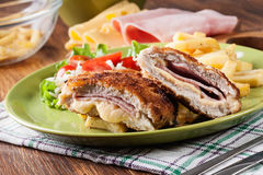 Kotelett Cordon bleu mit Schweinelende diente mit Pommes-Frites und Salat Lizenzfreie Stockfotografie