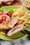 Kotelett Cordon bleu mit Schweinelende diente mit Pommes-Frites und Salat Stockfoto