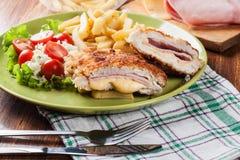 Kotelett Cordon bleu mit Schweinelende diente mit Pommes-Frites und Salat Stockfotografie