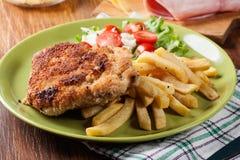 Kotelett Cordon bleu mit Schweinelende diente mit Pommes-Frites und Salat Lizenzfreies Stockbild