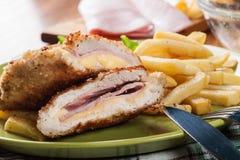 Kotelett Cordon bleu mit Schweinelende diente mit Pommes-Frites und Salat Stockbild