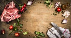 Kotelett della carne di maiale con gli ingredienti freschi per la cottura - erbe, spezie e pomodori Strumenti d'annata della cuci immagini stock libere da diritti