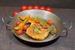 Kotelett mit Kartoffel zwängt, Tomaten, der grüne Spargel, geschmückt stockfotografie