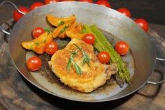 Kotelett mit Kartoffel zwängt, Tomaten, der grüne Spargel, geschmückt lizenzfreie stockbilder