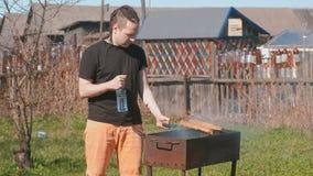 Koteletten van het jonge mensen de roosterende rundvlees met brood op de grill stock footage
