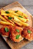 Koteletten van Turkije dienden met gebraden gerechten op scherpe raad en op een oude houten achtergrond Koteletten van het fijnge Stock Afbeeldingen