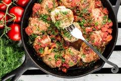 Koteletts in der Bratpfanne mit Gabel Die Türkei-Fleischklöschen mit Tomatensauce stockfotos