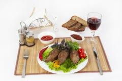 Kotletter med gräsplaner, tomater och gurkor Tjäna som med svart eller vitt bröd och ett exponeringsglas av rött vin royaltyfria foton