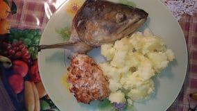 Kotletter, mosade potatisar och ett fiskhuvud på en platta/, Royaltyfria Foton