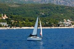Парусное судно плавать с белыми ветрилами на море Черногория, залив Kotor стоковое фото