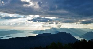 Kotor bay in the late afternoon with the sun shining through the clouds stock photography