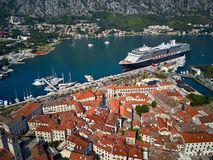 Kotor bay with moored cruise ship in Montenegro. Cruise ship in a port of Kotor in Montenegro. In front of it there are old houses with red-orange shingled roofs royalty free stock images