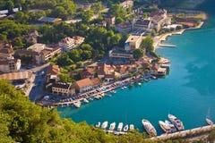 KOTOR, MONTENEGRO - 11 DE JULIO DE 2015: Edificios y yate viejos Pier Marina en el mar adriático en la ciudad vieja de Kotor Imagen de archivo libre de regalías