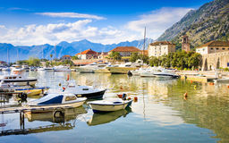 KOTOR, MONTENEGRO - JUNE 24, 2015: The boats in sea at sunset with mountains and old city in the background Royalty Free Stock Photo