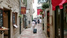 Kotor, Montenegro - 27 June, 2017. Senior women carrying luggage walking through narrow street of old city by stones
