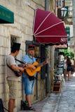 Kotor - Montenegro - 17mo de julio de 2016 Dos ejecutantes con la guitarra, una pared de piedra de la calle en el fondo Fotos de archivo libres de regalías