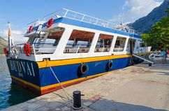 Pleasure boat near embankment before departure for excursion, Kotor, Montenegro. KOTOR, MONTENEGRO - SEPTEMBER 10, 2017: Unknown tourists are on embankment near Royalty Free Stock Photography