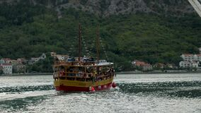 Yellow wooden double-deck boat with tourists sails from the shore on a trip