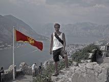Kotor, muchacho y bandera de Montenegro Imagen de archivo