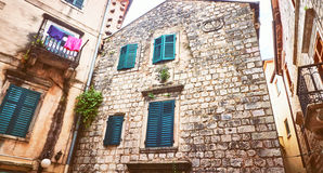 Kotor narrow small streets of  historical old town. House drying linen  bright sun blind old stone. Authentic structures. No body Stock Photography