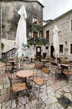 Kotor. Rain. KOTOR, MONTENEGRO - MAY 17, 2013: Tables of a street cafe on a square of Kotor, Montenegro; them are empty by rain. On May 17, 2013 in Kotor Royalty Free Stock Images
