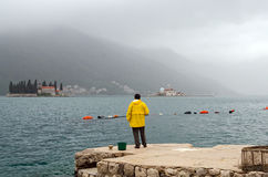 Kotor's Bay. Fisherman. KOTOR'S BAY, MONTENEGRO - MAY 17, 2013: A man fishes in front of the two islands of the Bay of Kotor, Montenegro. On May 17, 2013, in Royalty Free Stock Photography