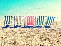 Kou op strand met retro bed van de strepenzon Stock Afbeelding