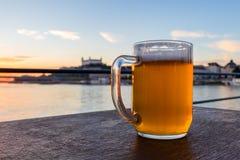 Koud glasmok bier met schuim op het kasteel achtergrond van Bratislava, Slowakije stock foto